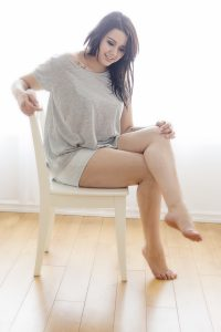 Full length shot of a beautiful attractive plus size young fashion model wearing gray top and shorts sitting on chair.